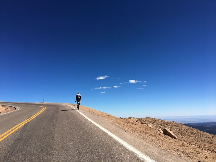 Rear view of man riding bicycle on road against clear blue sky