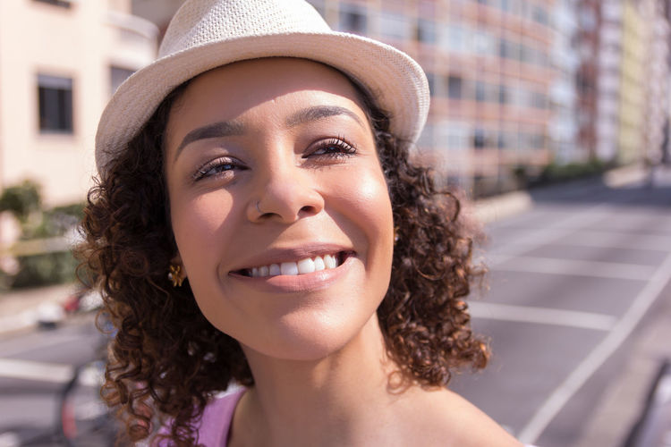 Smiling Young Woman Wearing Hat While Standing Against Buildings In City