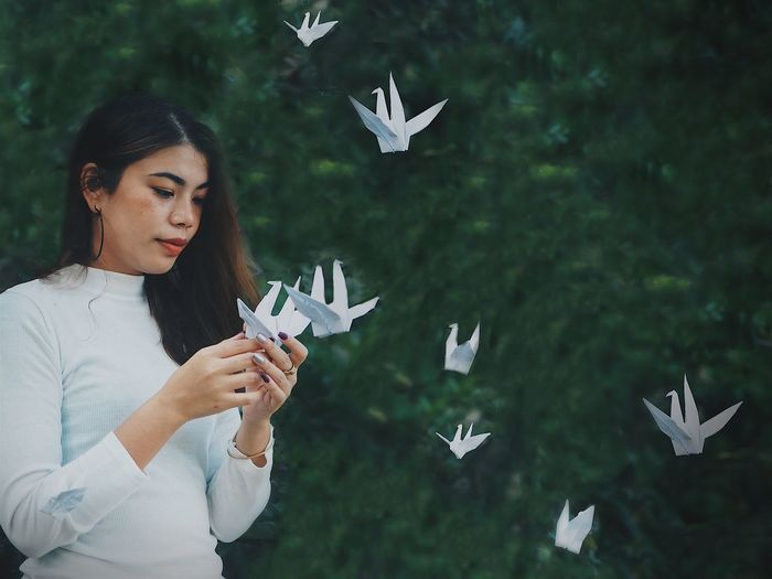 Young woman looking at paper bird against tree
