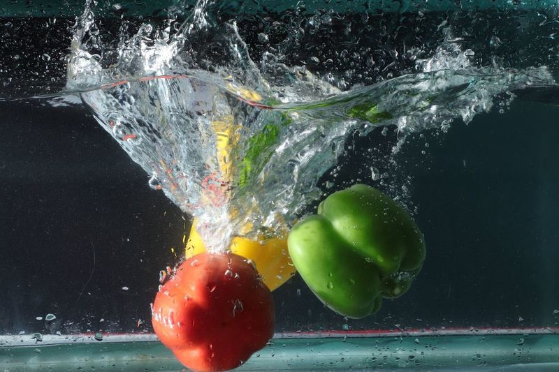 Close-up of bell peppers splashing in water