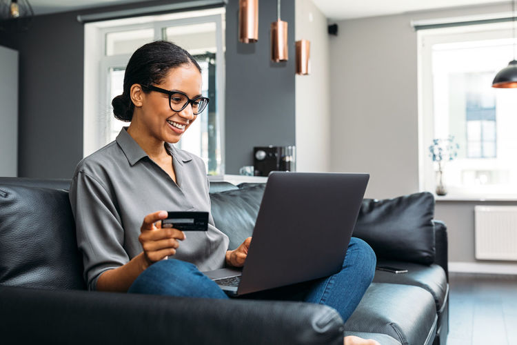 Woman doing online shopping while sitting on sofa