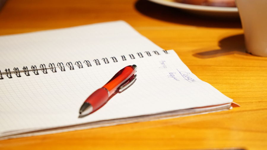Close-up of pen and spiral notebook on wooden table