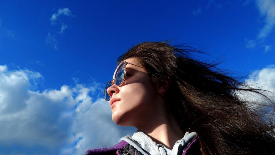 Low Angle View Of Thoughtful Young Woman Wearing Sunglasses Against Blue Sky