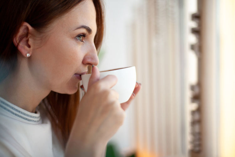 Portrait of young woman drinking coffee