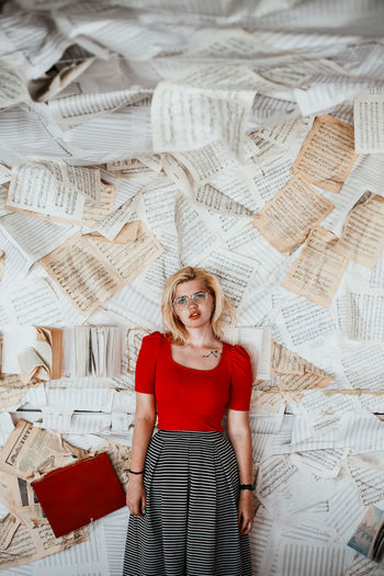 Portrait of woman against papers on wall