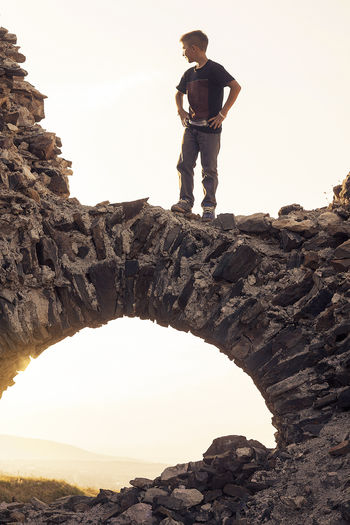 Low angle view of man standing on rock formation against clear sky