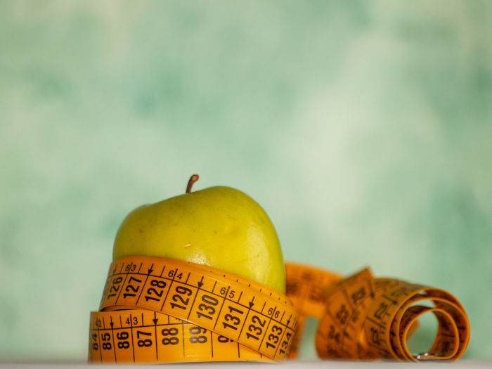 Apple Diet Diet & Fitness Food And Drink Healthcare Measuring Measuring Tape Obesity Slim Apple - Fruit Body Positive  Close-up Colored Background Communication Concept Conceptual Dieting Fat Focus On Foreground Food Food And Drink Freshness Fruit Healthy Healthy Eating Healthy Lifestyle Indoors  Lifestyles No People Number Red Sacrifice Slim Down Still Life Studio Shot Tape Measure Text Vitamin Wellbeing Yellow