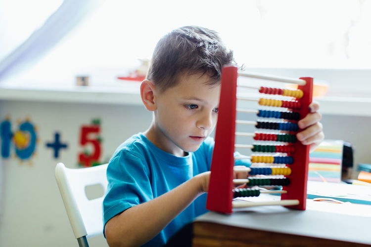 Close-Up Of Boy Using Abacus