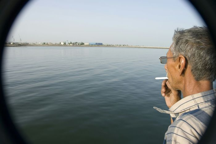 Awaiting Arrival Man Smoke Restless Cigarrette Island Water Sea On Boat Blue Travel