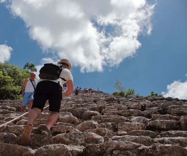 Low angle view of people walking on old ruin steps against cloudy sky
