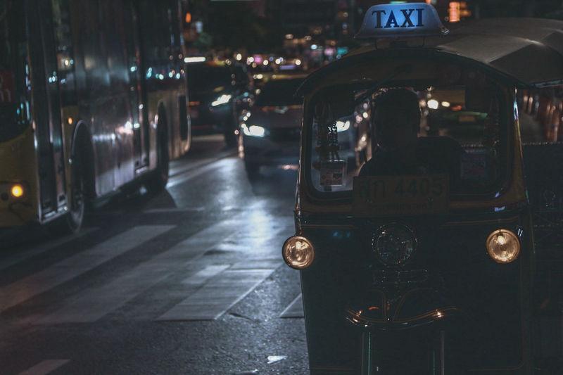 Jinrikisha on road in city at night