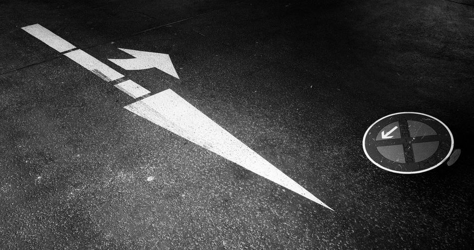High Angle View Of Arrow Symbol On Road