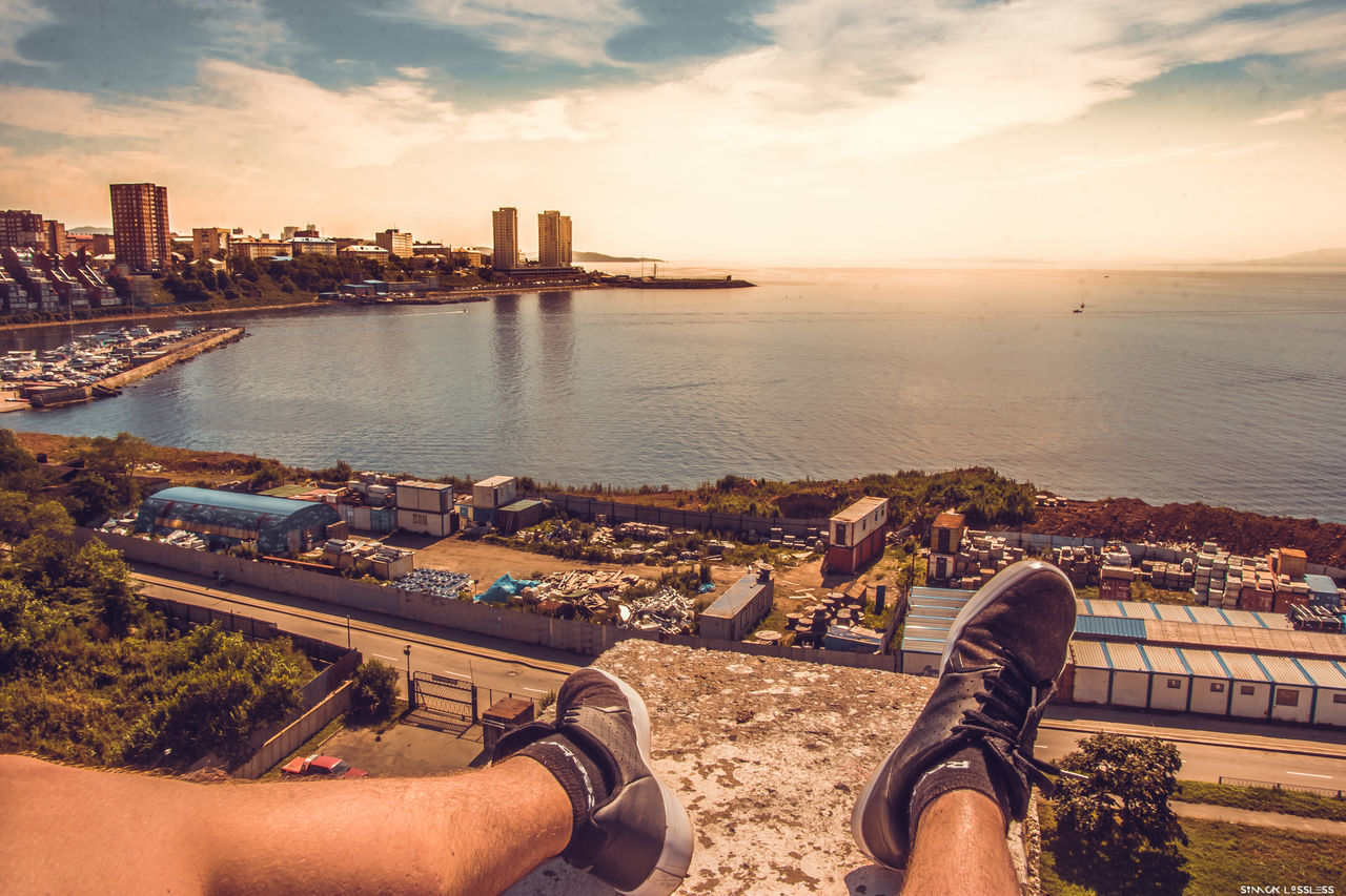 human leg, real people, water, personal perspective, low section, men, architecture, built structure, sea, building exterior, leisure activity, sky, human body part, cloud - sky, outdoors, cityscape, city, lifestyles, sunset, day, women, nature, skyscraper, people