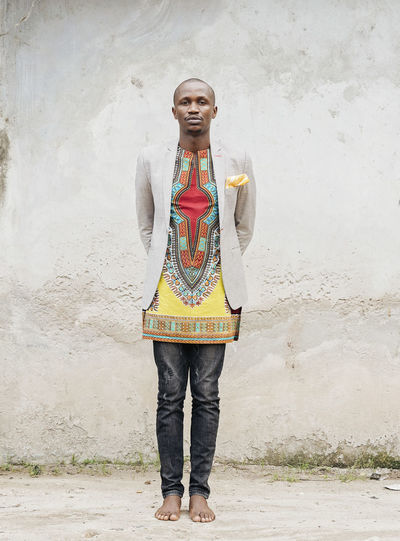 Black Model Standing African Fashion African Fabric Jeans Blazer - Jacket Bear Foot Looking At Camera Fashion Fashion Model Fashion Photography One Person Front View Real People Casual Clothing Full Length Wall - Building Feature Leisure Activity Day Lifestyles Portrait Young Adult Smiling Young Men Architecture Outdoors