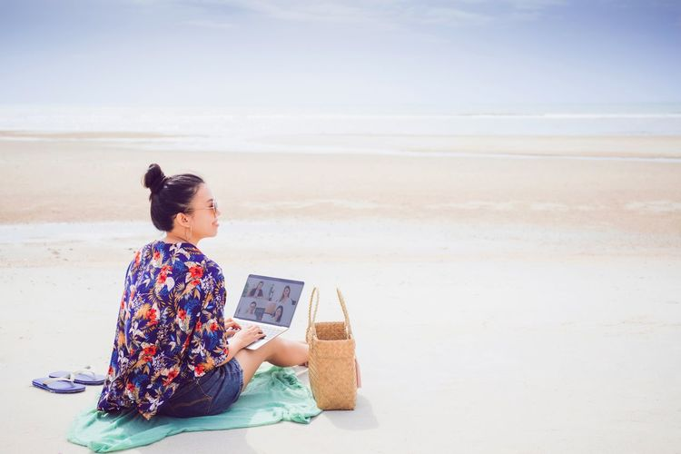 Woman sitting on shore at beach against sky