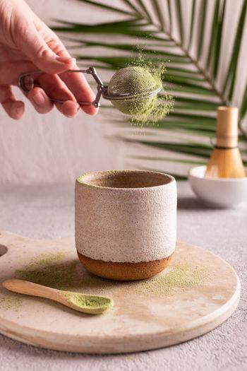 Woman preparing green matcha tea