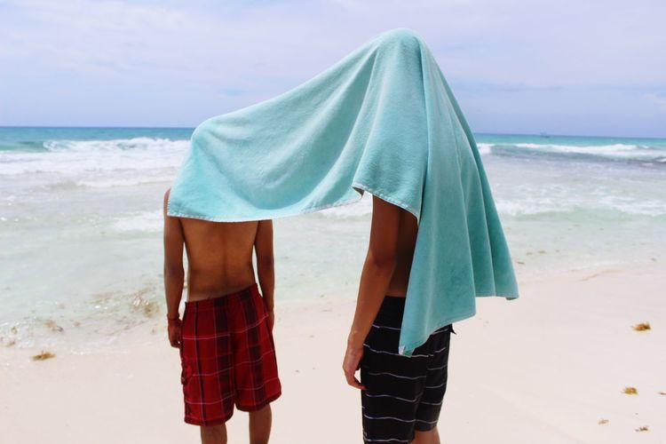 People with towel on face standing at beach against sky