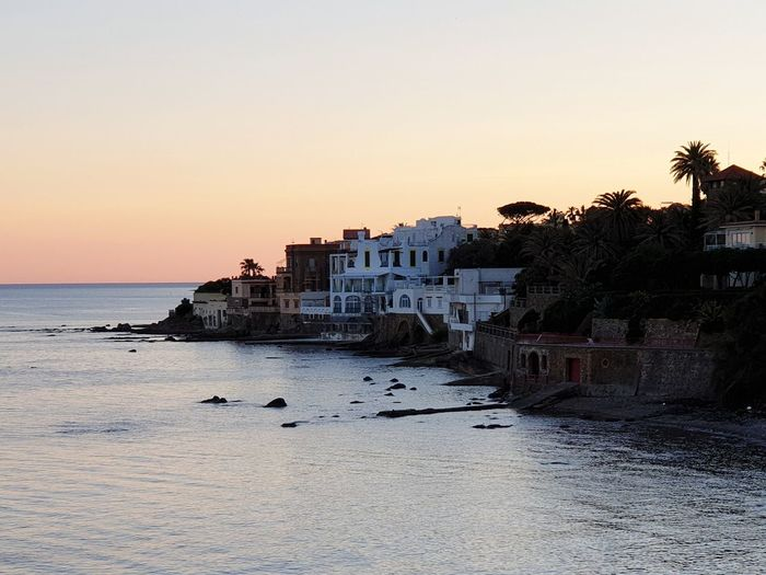 Sea and buildings against clear sky during sunset