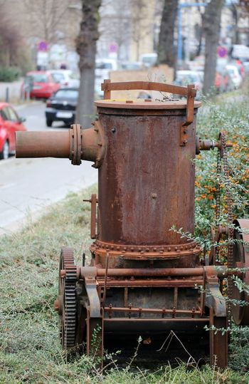 Close-up of rusty machine part on field