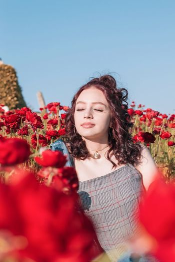 Beautiful young woman sitting amidst red poppy flowers against sky