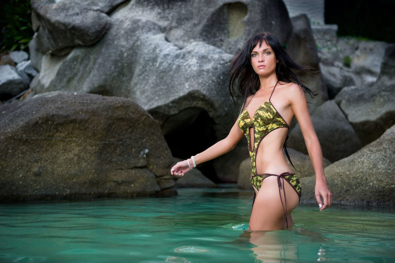 Portrait Of Beautiful Woman Standing In Sea Against Rocks