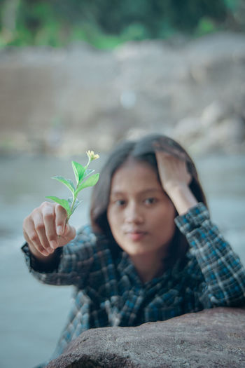 Portrait of boy holding plant