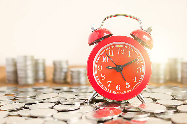 Close-Up Of Alarm Clock On Coins At Table