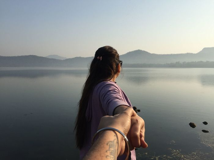 Cropped Image Of Boyfriend Holding Girlfriend Hand By Lake
