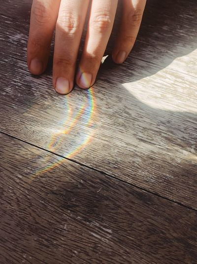 Rainbow Human Hand Human Body Part Hand One Person High Angle View Body Part Finger Sunlight Close-up Human Finger Unrecognizable Person Leisure Activity Real People Day Multi Colored Table Human Limb Shadow