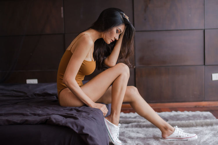 Sensuous young woman sitting on bed at home