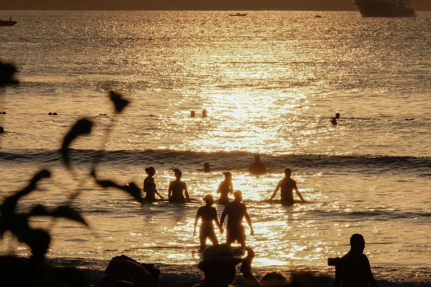 Sea Sunlight Silhouette Water Sunset Sea Outdoors Nature Large Group Of People Beach Men Day Leisure Activity Beauty In Nature Wave Real People Fun Lifestyles Sky Shadow People