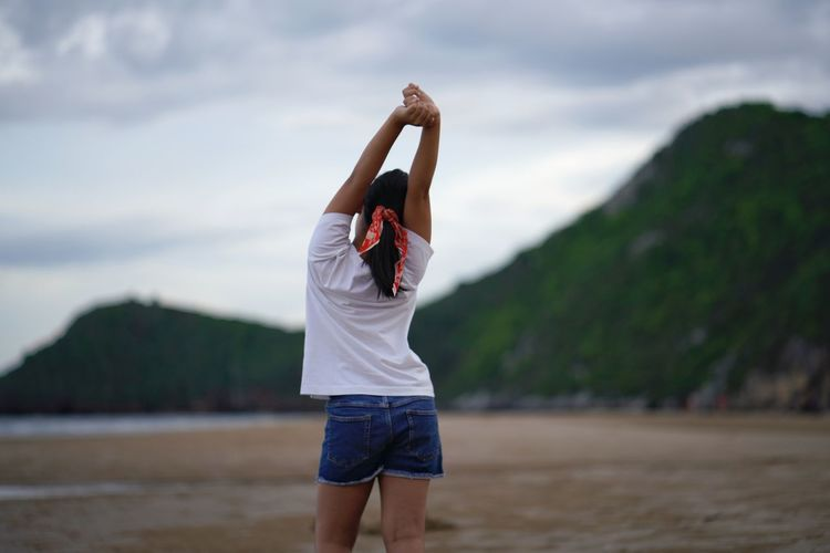 Rear view of girl standing on beach