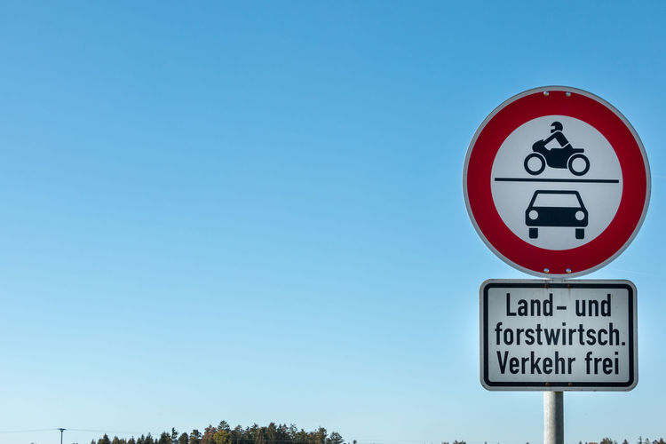 Traffic sign which allows agricultural and forestry vehicles to drive through Sign Communication Guidance Road Sky Road Sign Blue Text Clear Sky No People Low Angle View Day Human Representation Copy Space Warning Sign Representation Nature Information Geometric Shape Information Sign Outdoors Rules