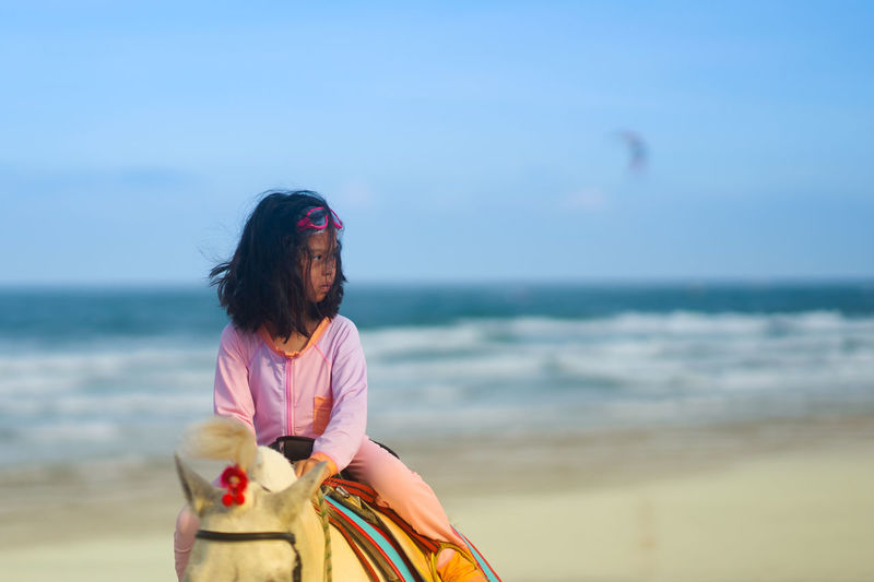 Woman on beach against sky