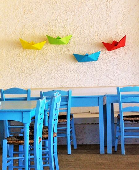 Chairs and tables by wall with paper boat decoration at restaurant