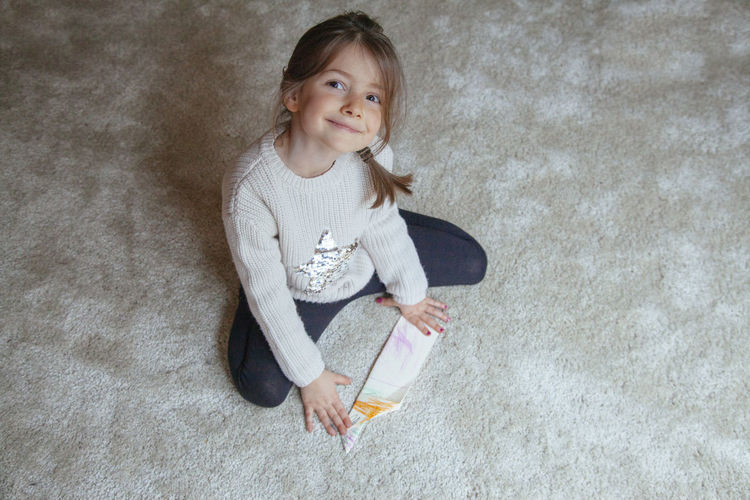 High angle portrait of girl playing with paper airplane
