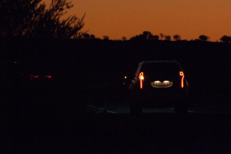 After Dark Car Dark Field Illuminated Land Land Vehicle Mode Of Transportation Night Orange Color Silhouette Sky Street Sunset Transportation