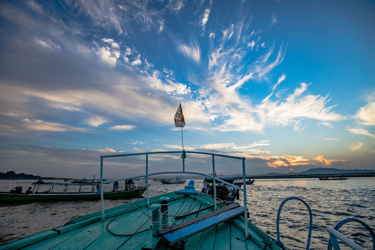 Fishing boat moored on sea against sky