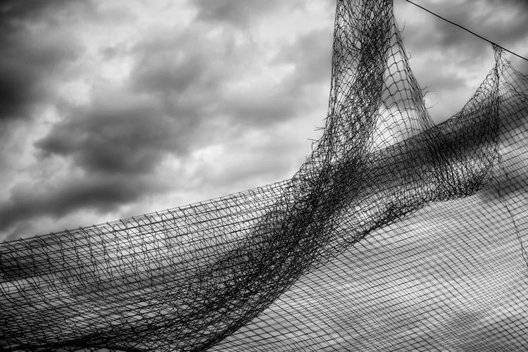Close-up of fishing net against cloudy sky