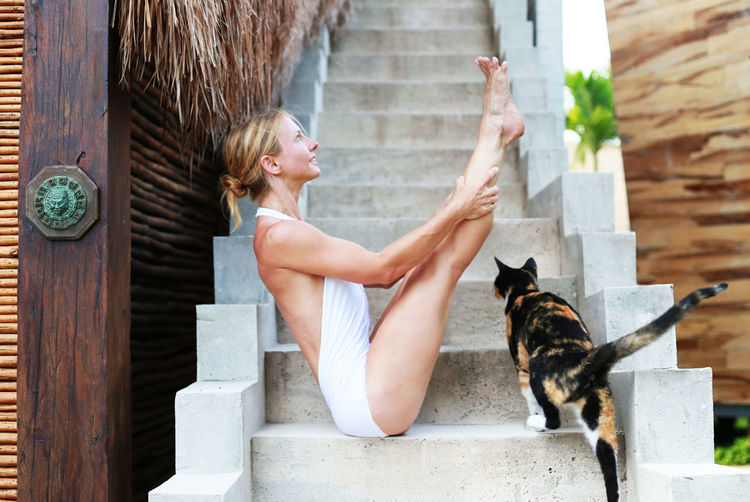 Woman practicing yoga by cat on staircase