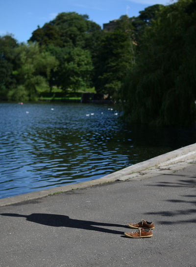 Shadow of man with shoes on footpath by lake