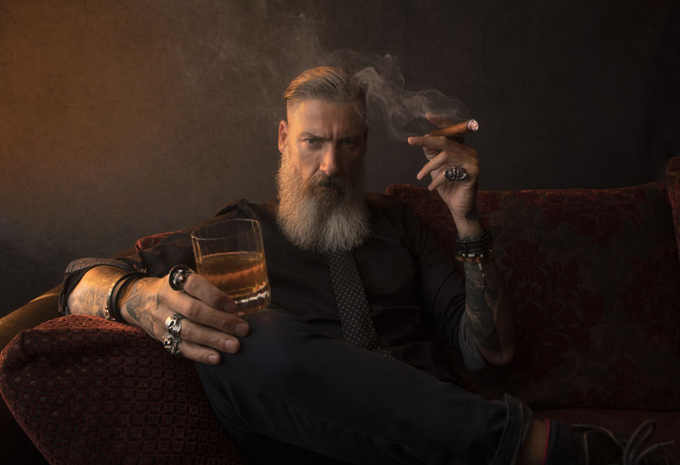 Portrait of an attractive business man with a cigar and a glass of whiskey in a dark room Isolated Adult Alcohol Beard Bearded Boss Businessman Cigar Cigarette  Club Drink Drinking Glass Hipster Holding Leger Lifestyles Men Millionaire Refreshment Sitting Smoking - Activity Studio Shot Successful Vintage Whiskey