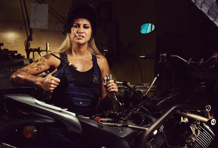 Woman Repairing Motorcycle While Smoking At Workshop