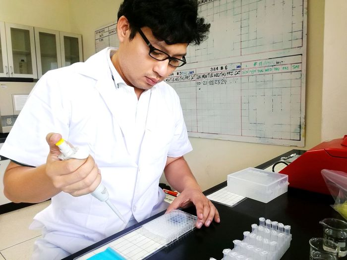 Mid Adult Man Holding Working In Laboratory