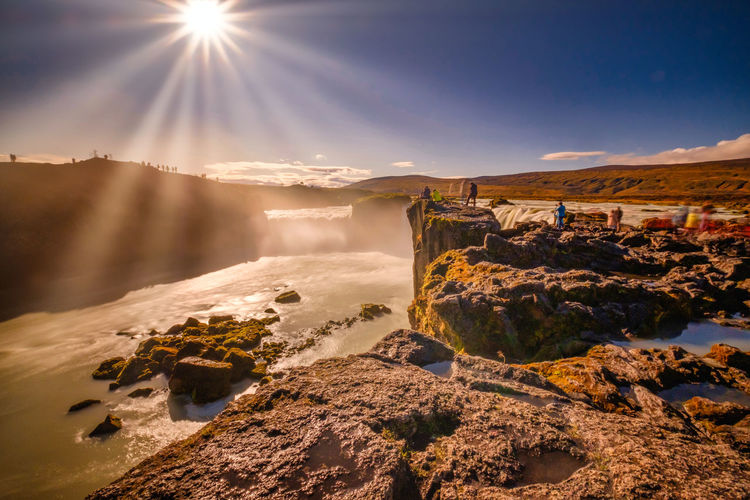 Goðafoss in long exposer, blue sky, warm autumn colors in the sun rays
