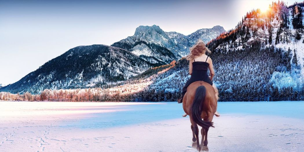 Rear view of woman riding horse on snow covered landscape against clear sky