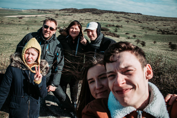 Portrait of smiling friends standing on landscape