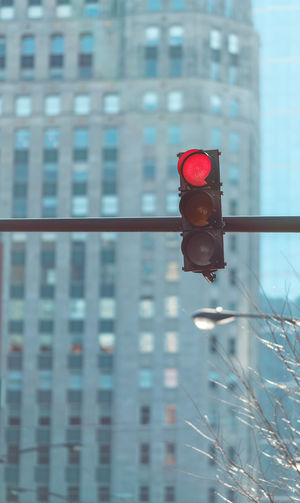 Close-up of red traffic light against buildings in city