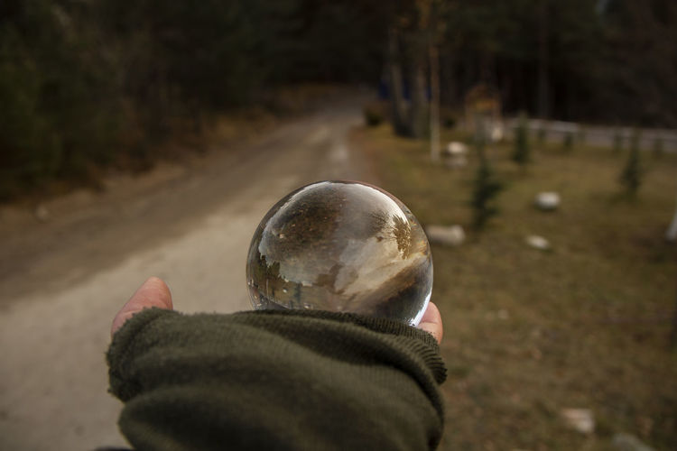 Cropped hand of person holding crystal ball on land