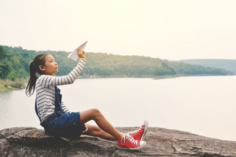 Side view of girl playing with paper airplane while sitting on rock against lake
